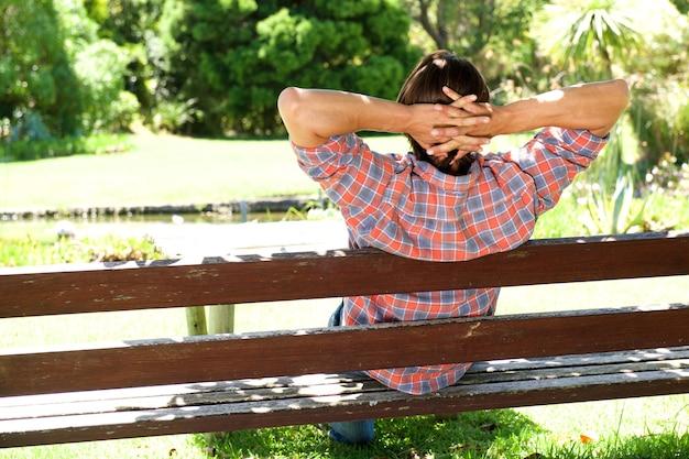 Derrière de jeune mâle se détendre sur un banc en bois dans le parc