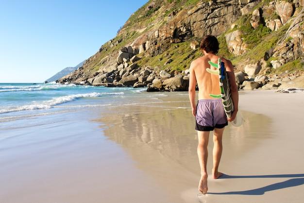 Derrière de séduisant surfeur marchant dans le sable par l'eau
