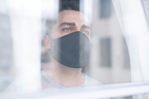 Derrière la vitre vue de sérieux jeune homme pensive en masque de tissu noir regardant par la fenêtre tristement à l'hôpital
