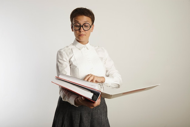 Désapprouver une enseignante portant un chemisier blanc, une jupe en tweed gris et des lunettes de classement des papiers dans des classeurs lourds isolés sur blanc