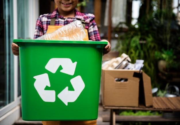 Descendance africaine tenant une boîte de recyclage de bouteilles en plastique