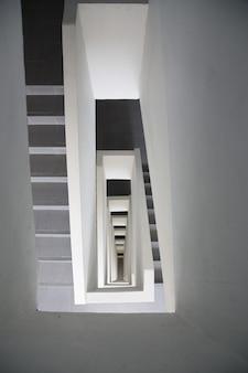 En descendant la spirale rectangulaire de l'escalier