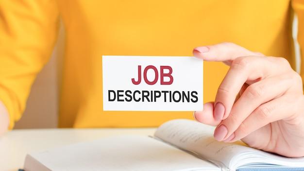 Les descriptions de poste sont écrites sur une carte de visite blanche. la main d'une femme tient une carte en papier blanc. concept commercial et publicitaire.