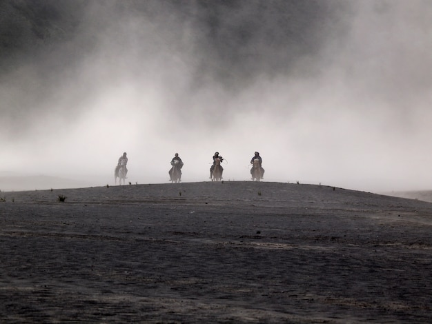 Désert de bromo et cavaliers pendant la tempête de sable à bromo