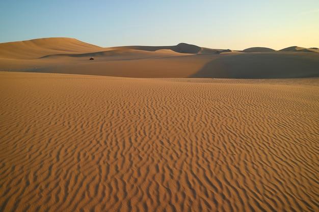 Désert de huacachina avec de belles ondulations de sable et un buggy au loin, ica, pérou