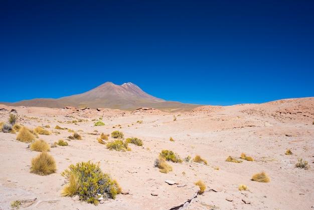 Désert rocheux et volcan fumant au loin