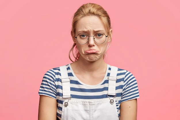 Désespérée, une jeune femme abusée courbe la lèvre inférieure en insatisfaction, habillée avec désinvolture, se sent déprimée en découvrant une nouvelle tragique, isolée sur rose