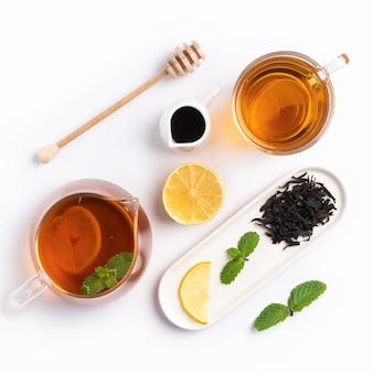 Design concept vue de dessus du thé noir au miel avec du citron jaune et des feuilles de menthe sur fond de tableau blanc.