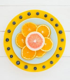 Design décoratif fait avec des tranches d'orange et de pamplemousse et des bleuets sur un bureau en bois