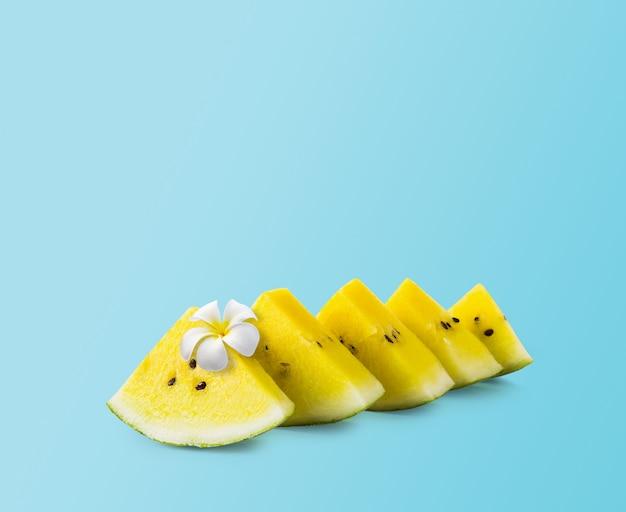Design été minime de melon d'eau jaune avec une fleur blanche sur fond bleu