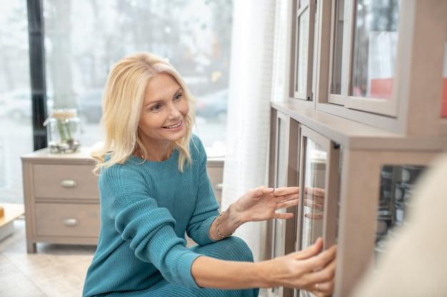 Design intéressant, placard. femme intéressée accroupie près d'une armoire vitrée, ouvrant une petite porte avec ses mains, avec délice.