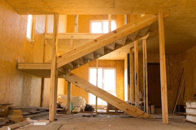 Design d'intérieur architectural en bois incomplet avec escalier, éclairé par la lumière du soleil