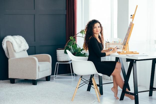 Design d'intérieur. belle artiste féminine aux cheveux bouclés travaillant sur des œuvres d'art au home studio.