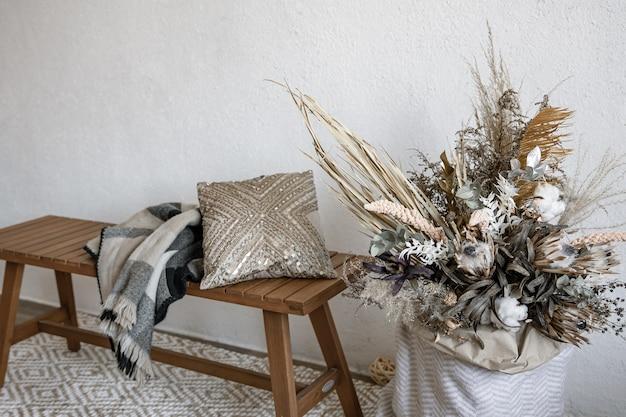 Design d'intérieur confortable dans un style scandinave avec des éléments décoratifs et une composition tendance de fleurs séchées.