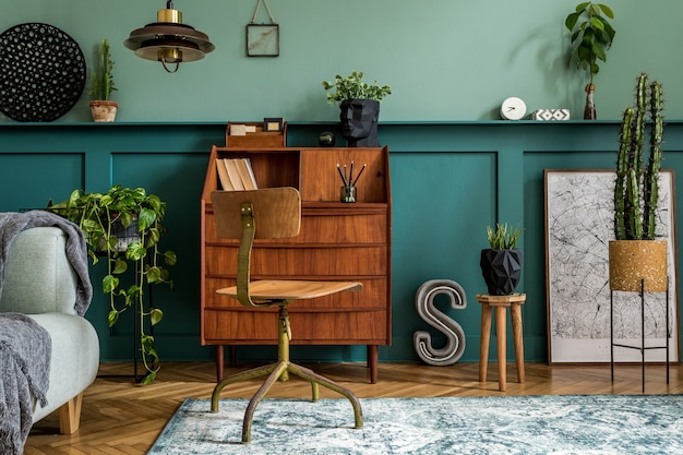Design d'intérieur élégant avec armoire en bois rétro, chaise, canapé élégant, plantes, cube, tabouret, décoration, affiche et accessoires personnels. concept rétro moderne d'espace de bureau à domicile. modèle.