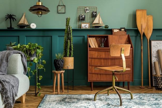Design d'intérieur élégant avec armoire en bois rétro, chaise, canapé gris, plantes, suspension, décoration, cartes, pagaie et accessoires personnels élégants. concept rétro moderne d'espace de bureau à domicile.