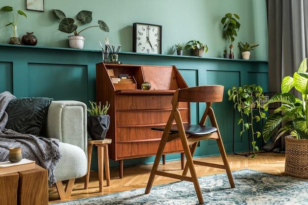 Design d'intérieur élégant avec armoire en bois rétro, chaise, canapé à la menthe, beaucoup de plantes, horloge vintage, décoration et accessoires personnels élégants. concept rétro moderne d'espace de bureau à domicile..