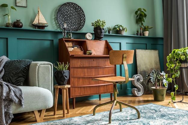 Design d'intérieur élégant avec armoire en bois rétro, chaise, canapé à la menthe, plantes, tapis, décoration, cartes, tabouret et accessoires personnels élégants. concept rétro moderne d'espace de bureau à domicile. modèle.