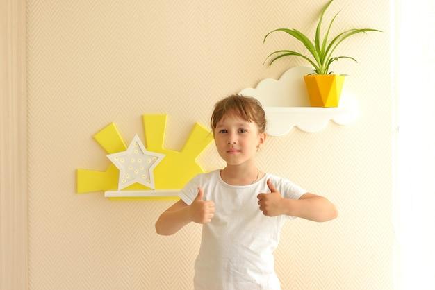 Design d'intérieur élégant et moderne. fille mode de vie heureux dans les nouvelles étagères de la pépinière. étagères pour enfants en forme de nuages blancs sur un mur beige uni, sur lequel se trouve un pot jaune avec une fleur.