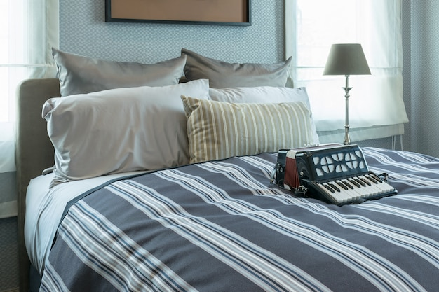 Design d'intérieur élégant avec oreillers à rayures et accordéon décoratif sur le lit