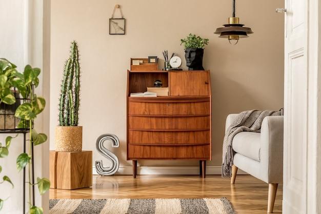 Design d'intérieur élégant et vintage d'espace ouvert avec armoire rétro en bois, canapé design, lampe à suspension, cactus à lettres néon, plantes et accessoires personnels élégants. décoration vintage moderne.