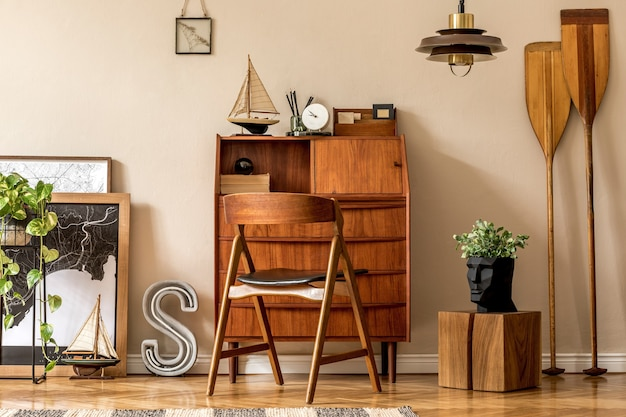 Design d'intérieur élégant et vintage d'espace ouvert avec armoire rétro en bois, chaise design, cartes, pagaie, bateau, cactus, plantes et accessoires personnels élégants.. décoration vintage moderne.