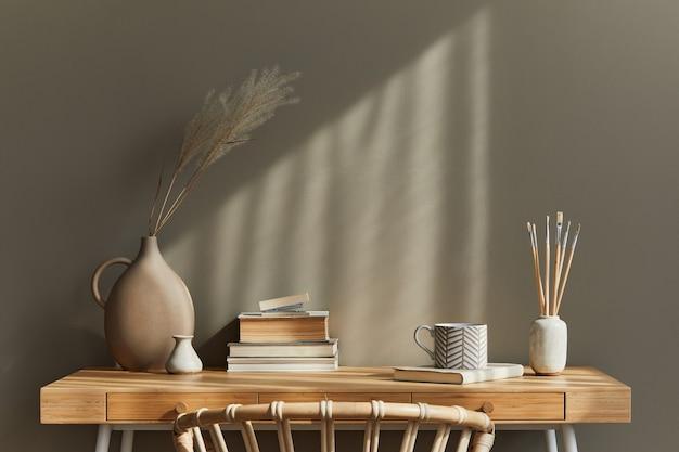 Design d'intérieur d'un intérieur de salon bohème neutre avec bureau élégant, fauteuil, fleurs séchées dans un vase, livre, décoration, fournitures de bureau, espace de copie, notes et accessoires personnels.
