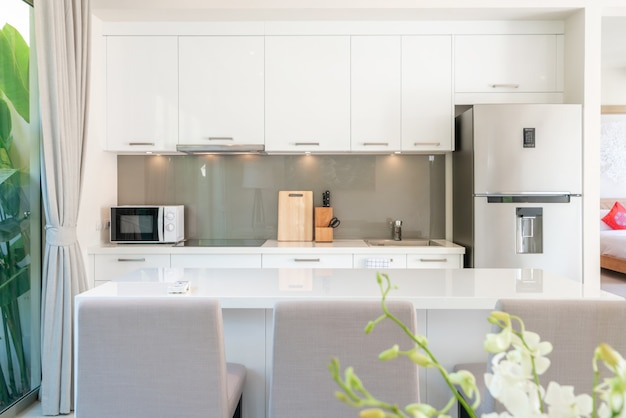 Design intérieur de luxe dans le salon des villas avec piscine. espace aéré et lumineux avec haut plafond surélevé et coin cuisine avec table à manger