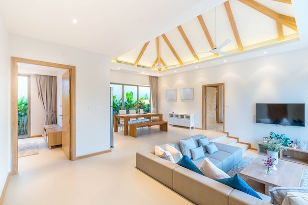 Design intérieur de luxe dans le salon des villas avec piscine. espace aéré et lumineux avec haut plafond surélevé et table à manger en bois