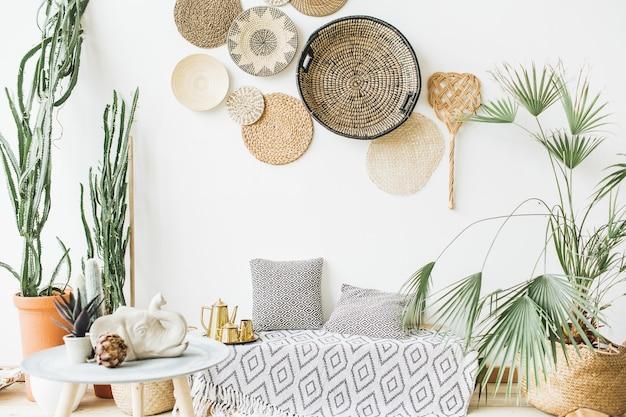 Design d'intérieur à la maison. coussins, théière dorée, assiettes décoratives en paille, couverture scandinave, palmier tropical, succulentes et décorations