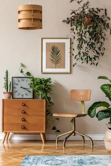 Design d'intérieur rétro du salon avec chaise et commode vintage design, plantes, cactus, horloge, accessoires personnels et cadre doré sur le mur beige. décor à la maison élégant..