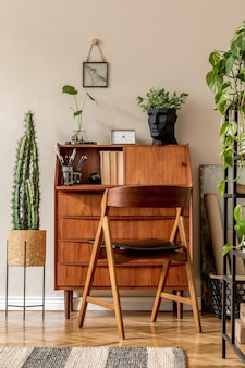 Design d'intérieur rétro de la salle d'atelier d'art avec bureau et chaise vintage en bois, plantes d'étagère, cactus, livres, photos et accessoires personnels élégants. décor à la maison vintage élégant. mur beige..