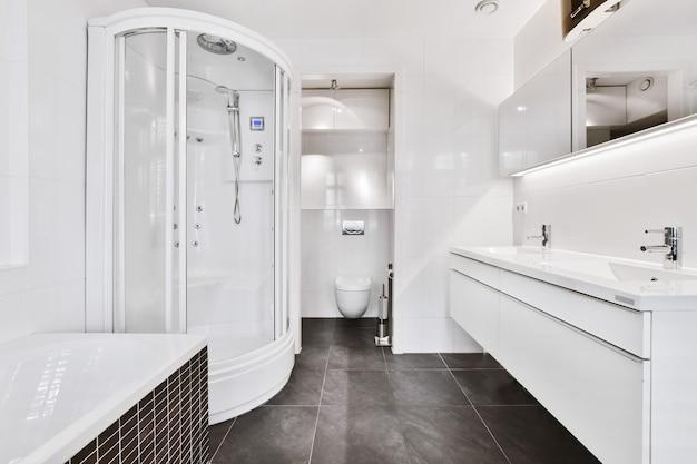 Design d'intérieur d'une salle de bains spacieuse et moderne avec des fenêtres à volets et un sol en marbre gris meublé avec des armoires blanches et un miroir dans un appartement de luxe