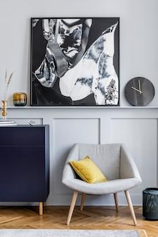 Design d'intérieur de salon avec commode élégante bleu marine, fauteuil gris, oreiller, horloge noire, fleur séchée, peintures modernes, décoration et accessoires élégants dans la décoration intérieure.