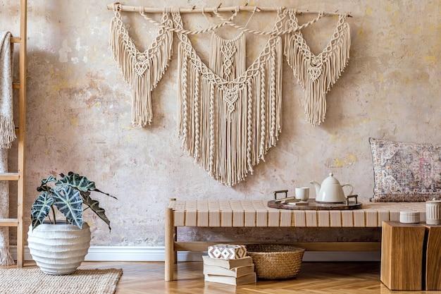 Design d'intérieur d'un salon élégant avec chaise longue beige, beau macramé, cube en bois, échelle, plantes, théière sur le plateau et accessoires personnels élégants. concept oriental de décoration intérieure.