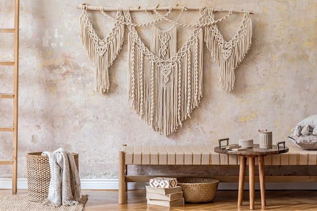 Design d'intérieur d'un salon élégant avec chaise longue beige, beau macramé, panier en rotin, échelle, livres, théière sur le plateau et accessoires personnels élégants. concept oriental de décoration intérieure.