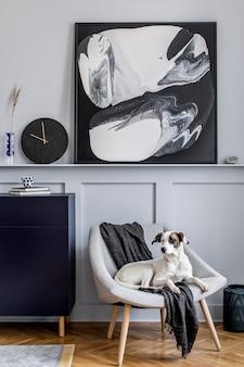 Design d'intérieur de salon avec fauteuil élégant, plaid, horloge noire, cactus, tabouret en marbre, peintures modernes, décoration et beau chien allongé sur le fauteuil.