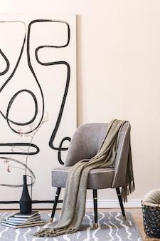 Design d'intérieur de salon avec fauteuil gris élégant, peintures abstraites sur le mur, fleurs dans un vase, oreiller, plaid et accessoires personnels élégants. concept beige. home staging moderne.