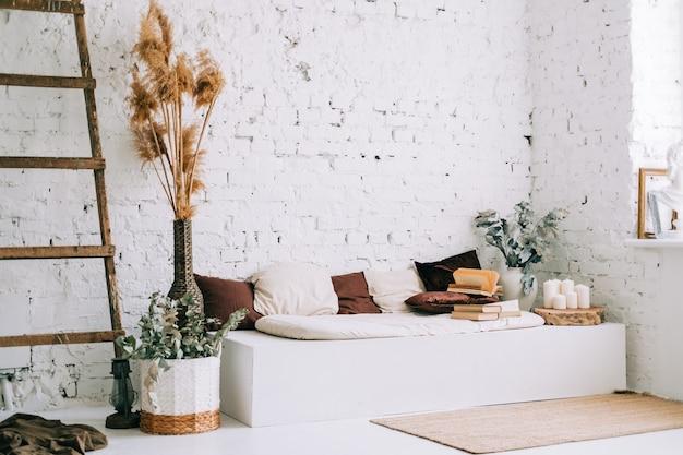 Design d'intérieur d'un salon lumineux avec des murs blancs et un banc de canapé avec des oreillers