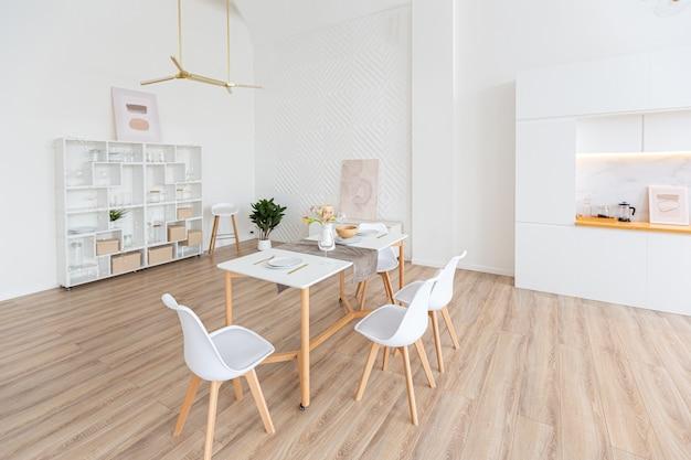 Design d'intérieur spacieux appartement lumineux dans un style scandinave et des tons blancs et beiges pastel chaleureux. mobilier tendance dans le salon et détails modernes dans le coin cuisine.
