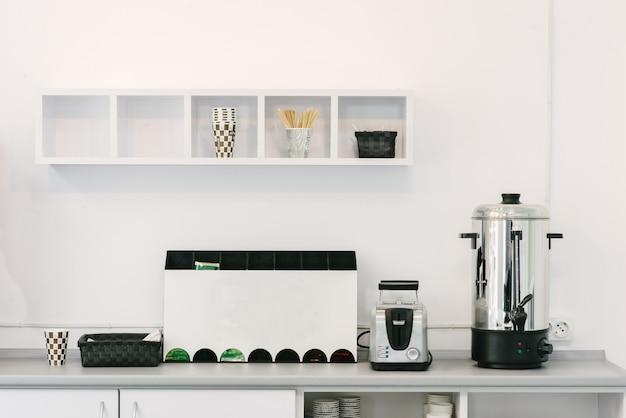 Design minimaliste moderne de la cuisine. appareils ménagers sur la table de la cuisine au bureau. cuisine de bureau.