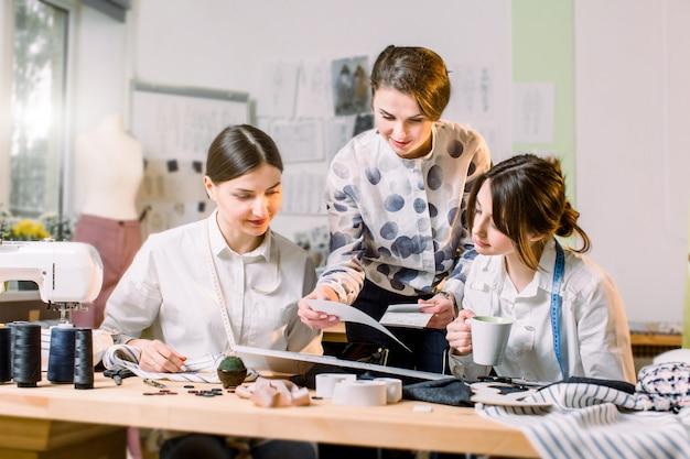 Design de mode, couturière, concept de tailleur. trois jeunes couturières de race blanche travaillant ensemble à l'atelier lumineux, préparant une nouvelle collection de vêtements faits à la main