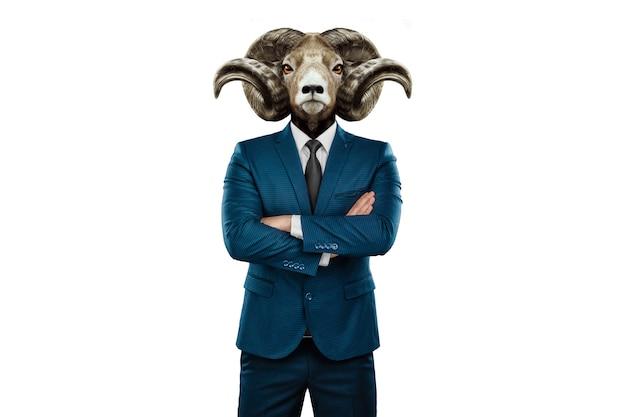 Design moderne, un corps humain dans un costume d'affaires avec la tête d'une chèvre à cornes sur fond blanc.