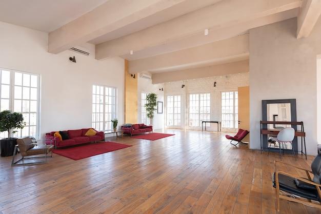 Design moderne d'une immense pièce blanche et lumineuse avec deux canapés rouges et de nombreuses grandes fenêtres. plein de soleil. plafond haut et parquet en bois