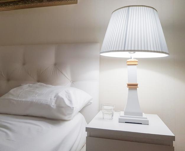 Design moderne de luxe d'une chambre lumineuse avec une table de chevet et une veilleuse et un oreiller sur le lit, se préparant au lit, un verre d'eau.