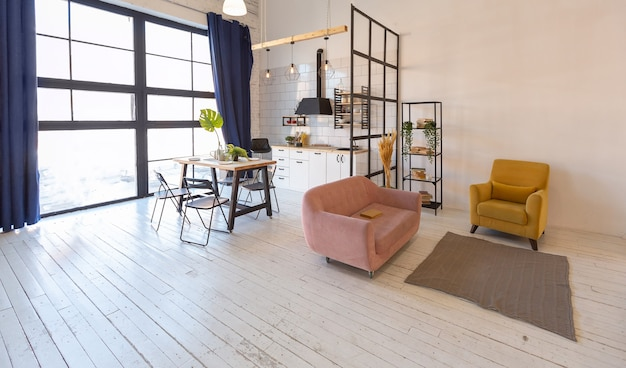 Design moderne de luxe d'un petit studio confortable de style scandinave avec des murs blancs, au deuxième étage avec une bibliothèque et une grande fenêtre haute pleine de lumière du jour
