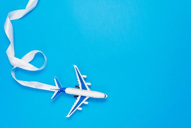 Design plat laïc du concept de voyage avec un avion sur bleu