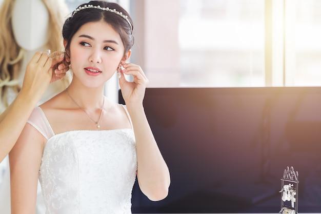 Designer asiatique travaillant dans un magasin de mode de mariage