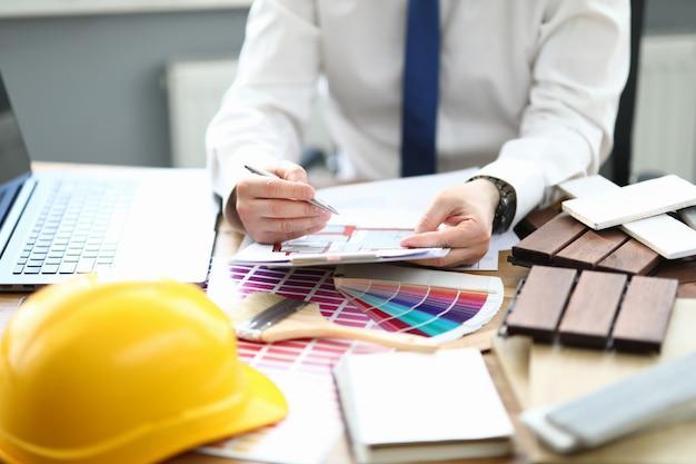 Designer au bureau est assis à table avec un projet et une palette de couleurs pour l'intérieur