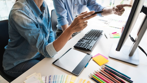 Designer créativité créative graphique travaillant ensemble la coloration à l'aide d'une tablette graphique et d'un stylet